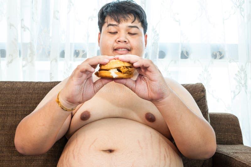 Fat man eating hamburger seated royalty free stock image