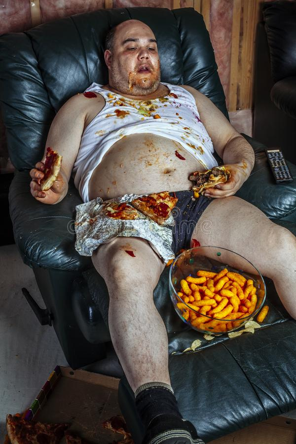 Fat man eating junk food and watching television royalty free stock images