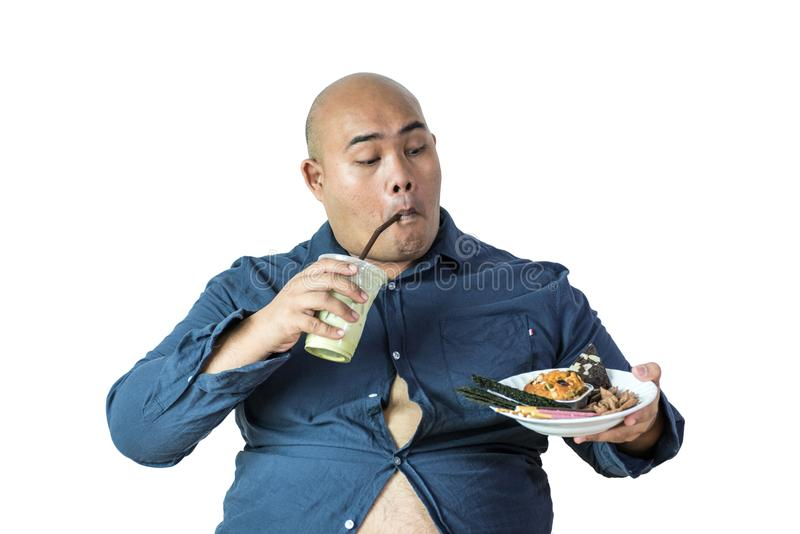 Fat man eating, portrait of overweight person feels hungry and e. Ating chips, cake, green tea frappe seated on armchai, isolated on white background with stock photo