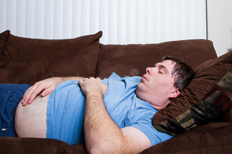 Fat man laying down. Man with his belly hanging out laying on the couch tired and asleep royalty free stock image