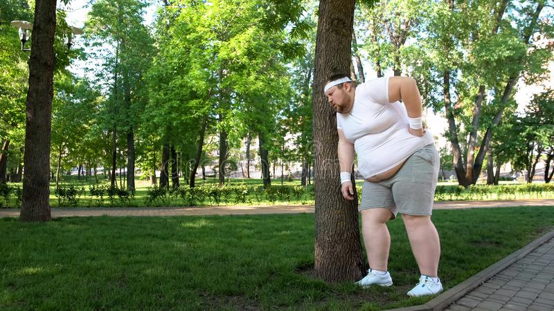 Fat man leaning on tree, tired after workout on fresh air, new healthy habit. Stock photo royalty free stock images