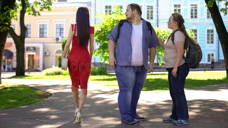 Fat man looking at beautiful lady in red passing by, obese girlfriend jealous stock images