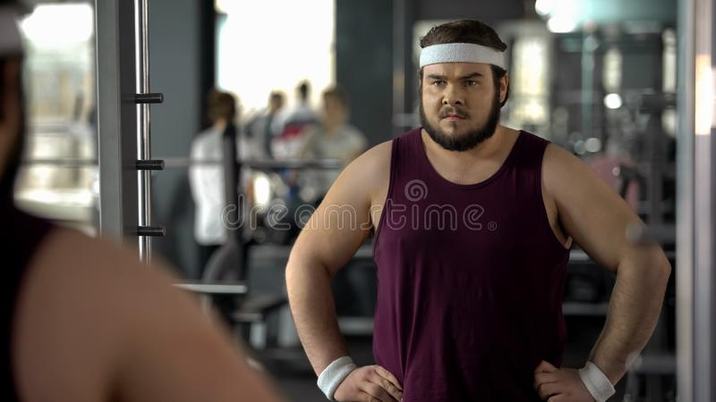 Fat man looking disappointed because of bad result after weight loss trainings. Stock photo royalty free stock image