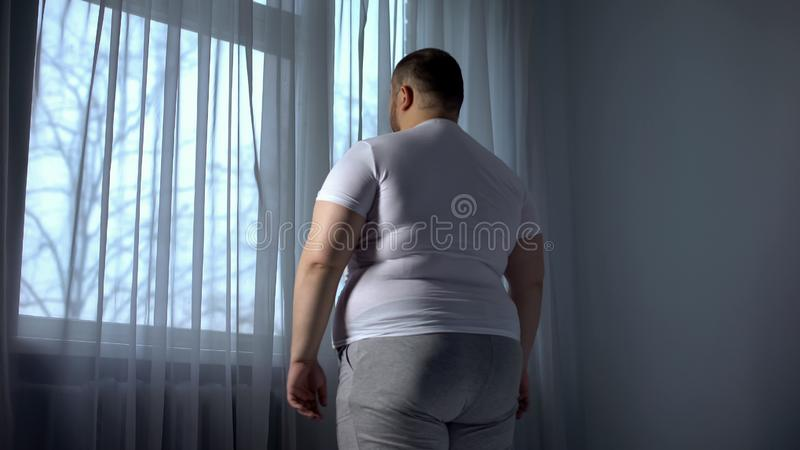 Fat man looking out through window, depressed introvert ashamed of obese body. Stock photo stock photos