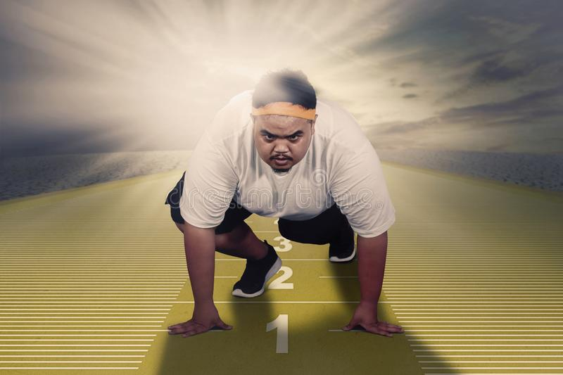 Fat man ready to run above measuring tape. Picture of an Asian fat man ready to run while kneeling above measuring tape. Shot with sunlight background stock illustration