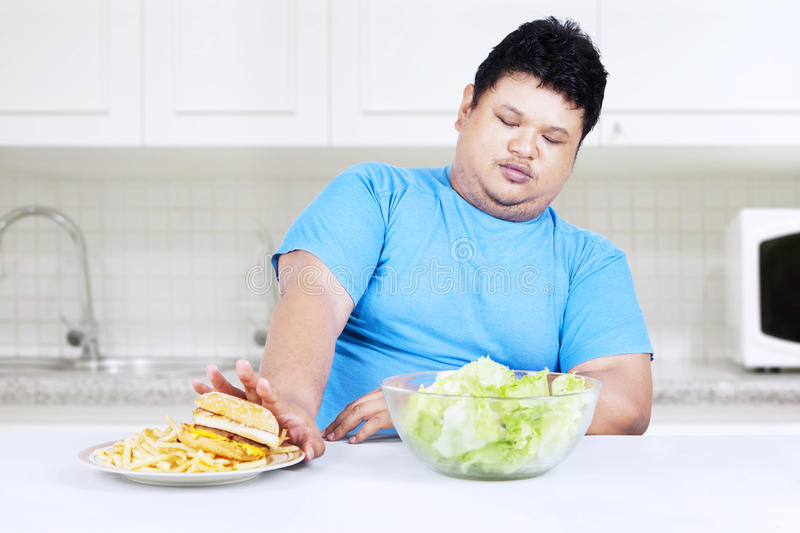 Fat man refuse junk food. And choose to eat healthy food royalty free stock images