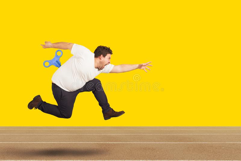 Fat man runs very fast without getting tired with extra energy stock photography