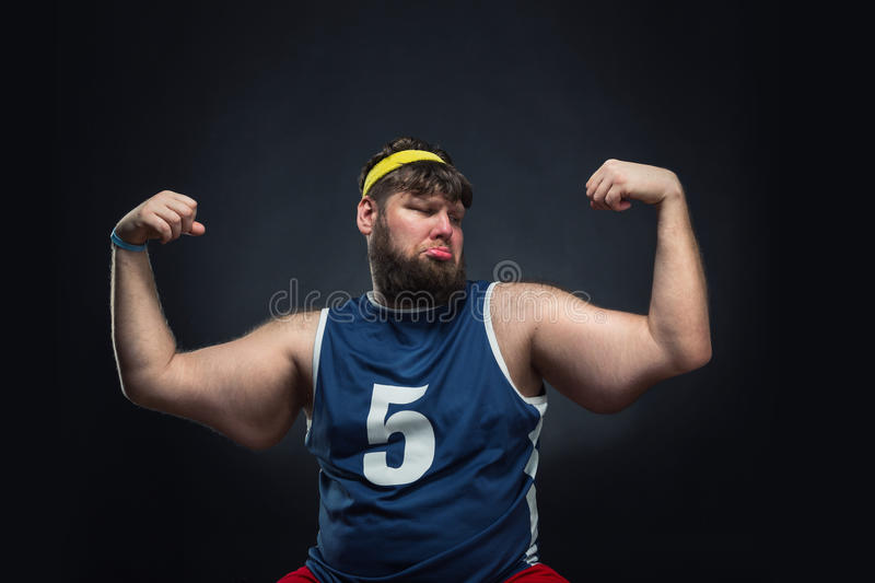Fat man shows his muscle. Over grey background stock image