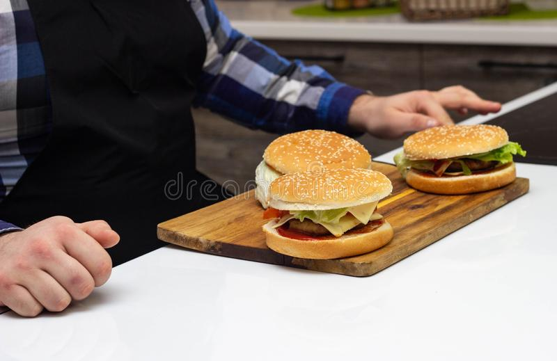 Fat man sitting in the kitchen waiting for the absorption of hamburgers and fast food, harmful food. Household royalty free stock images