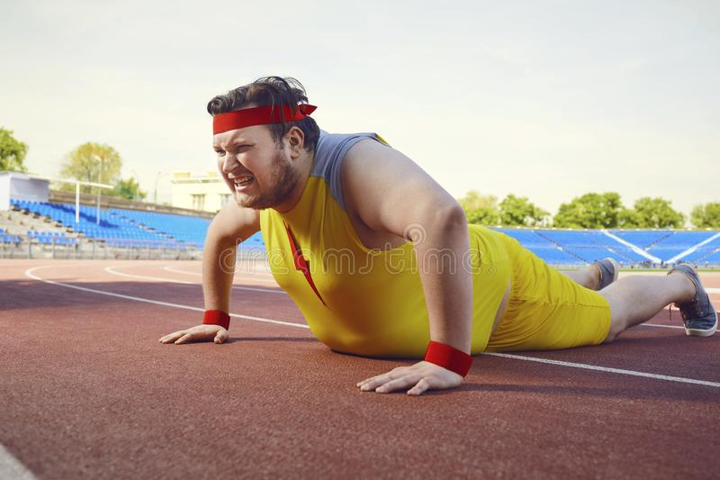 A fat man in sports clothes does push-up exercises. A fat man in sports yellow clothes does push-up exercises at the stadium stock image