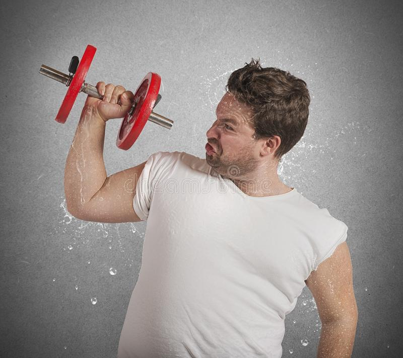 Fat man sweats. Fatigued fat man sweats while lifting weights stock images
