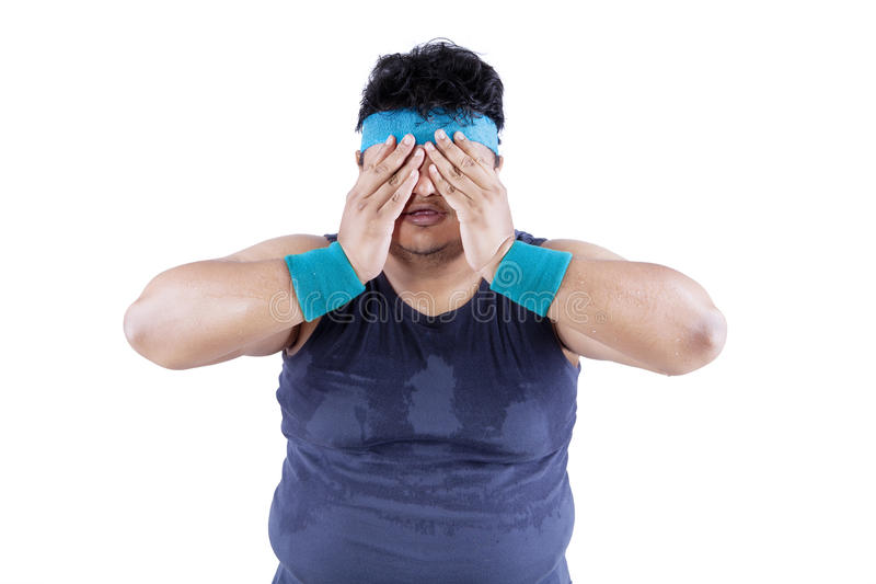 Fat man tired after workout 1. Fat man tired after workout and covering his face stock photography