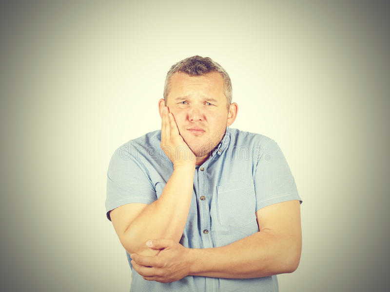 Fat man with a toothache. Isolated on background stock image