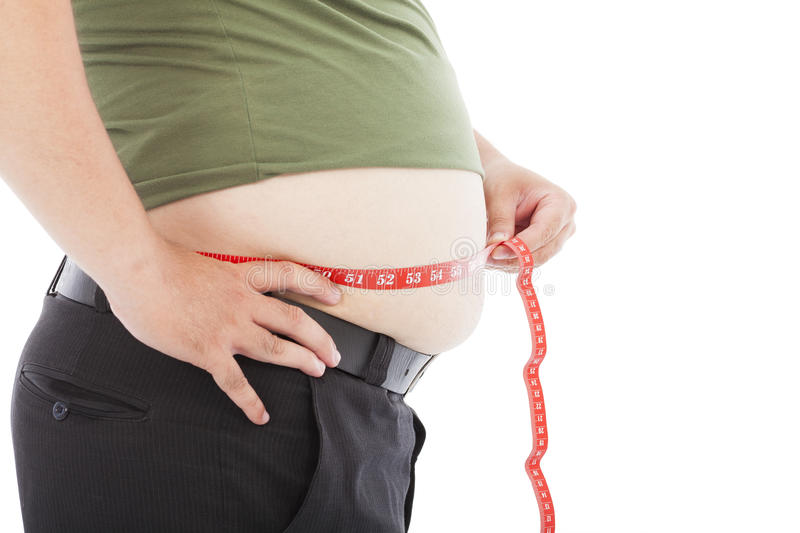 Fat man use scale to measure his waistline. In studio stock images