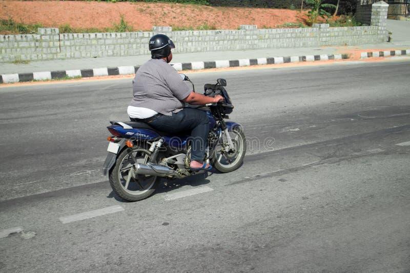 Fat motorcycle rider Indian. India, Karnataka - January 17, 2016: Fat motorcycle rider Indian. Overweight people adapt to life problems of the world: hypodynamia stock image