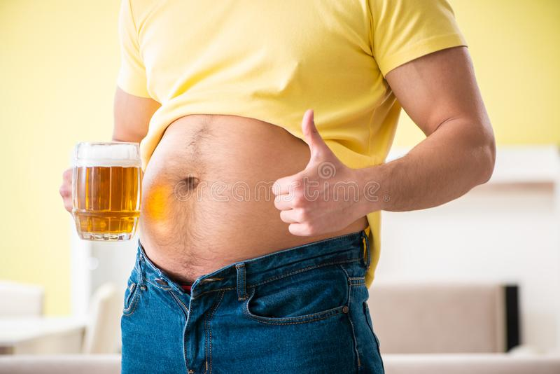The fat obese man holding beer in dieting concept stock photo