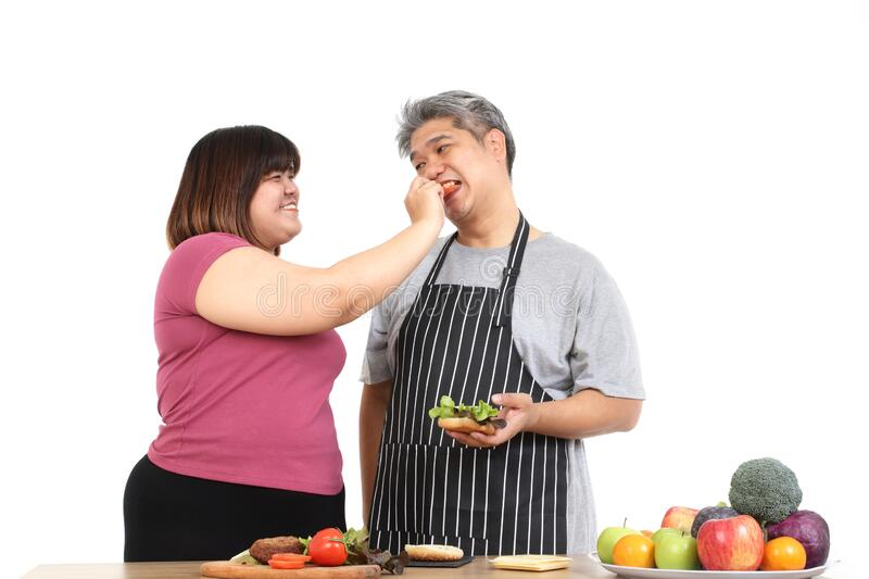 Fat people, both men and women, cook together, they are happy to eat. Fat people, men and women cook together, they are happy to eat. The concept of eating stock photos