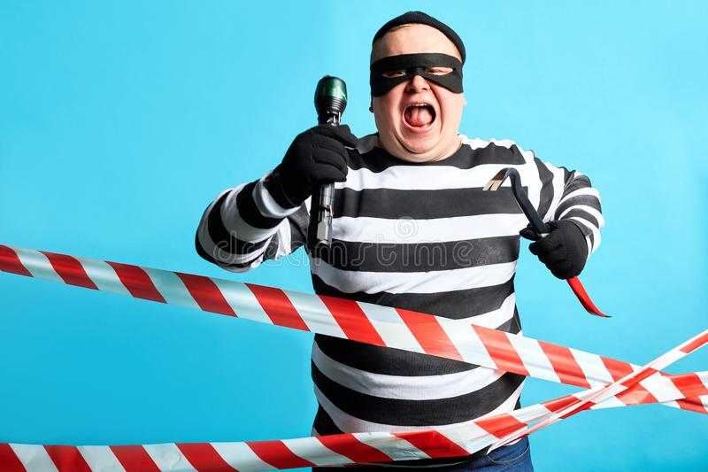 Fat plump burglar running away police royalty free stock photography