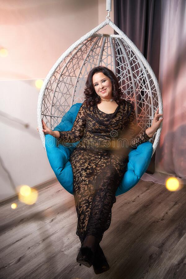 Fat plump charming cute woman with black curly hair in black beautiful dress in a white wicker chair royalty free stock photography
