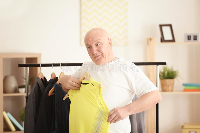 Fat senior man with small-sized clothes at home. stock photo