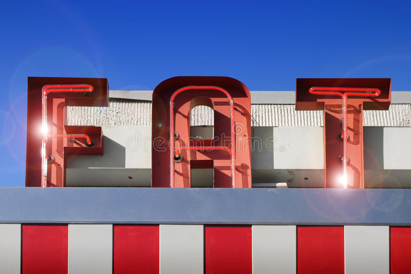 Fat sign. Red and white fat sign against blue sky stock image