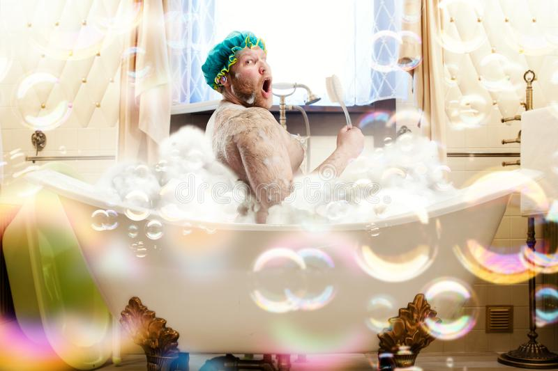 Fat ugly man washing in a bath stock photos