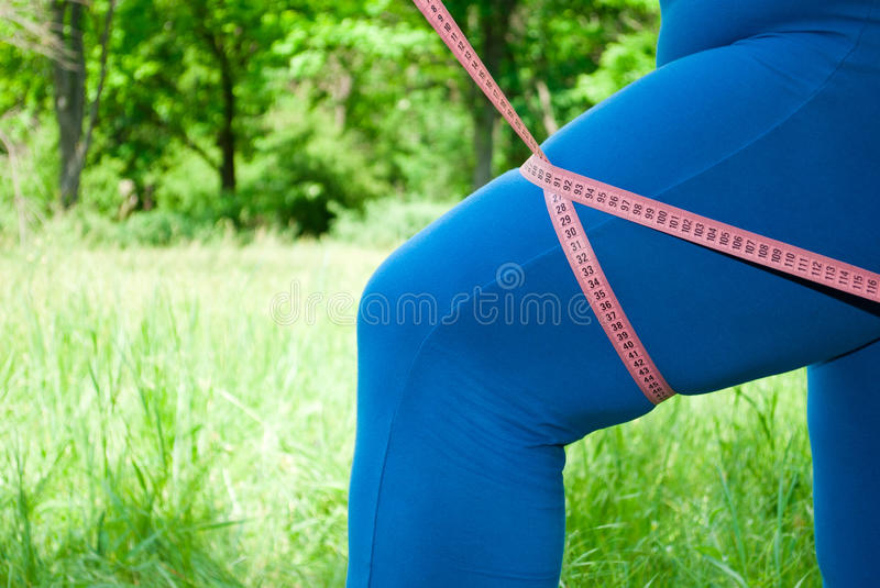 A fat woman in a blue suit on green grass measure the volume of the hip with a measuring tape stock photos