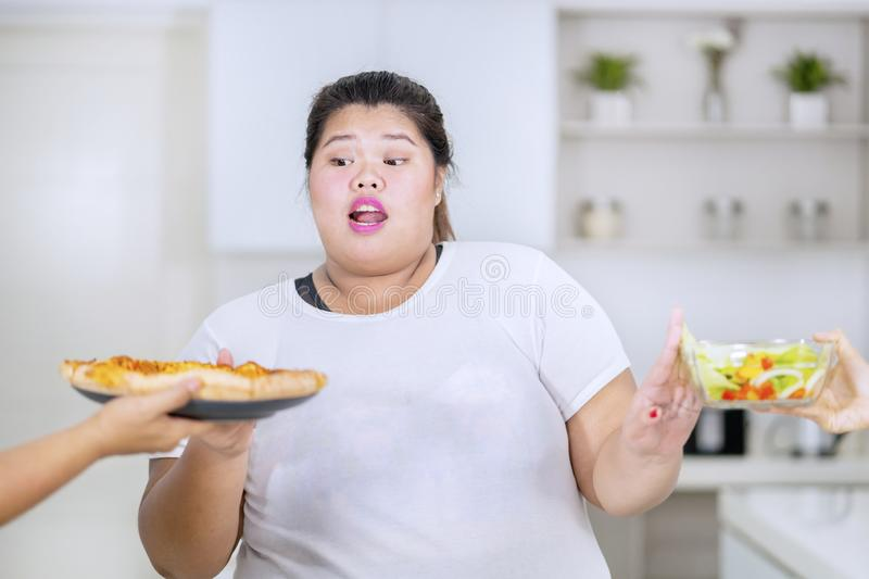 Fat woman chooses pizza over salad vegetables royalty free stock images