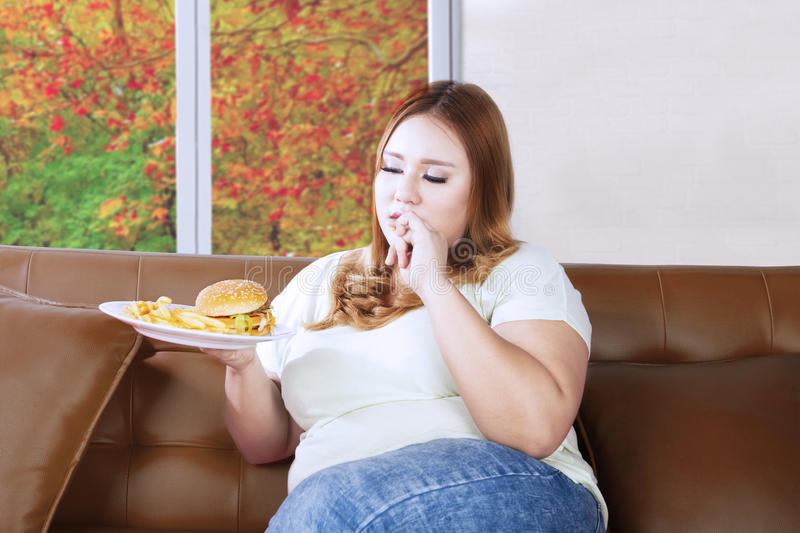 Fat woman eating junk food on the couch. Fat woman eating junk food on a plate while sitting on the couch with autumn background on the window royalty free stock photos