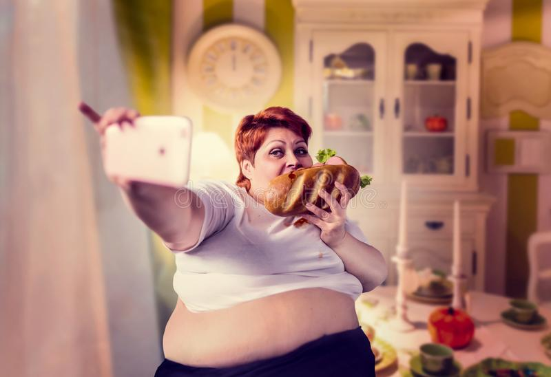 Fat woman eats sandwich and makes selfie, obesity royalty free stock photo