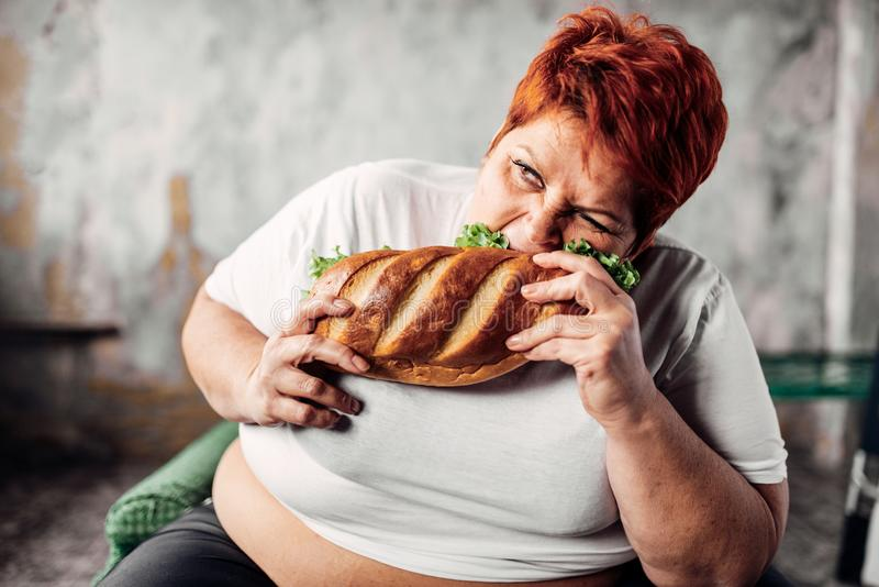 Fat woman eats sandwich, overweight and bulimic. Unhealthy lifestyle. Obesity stock images