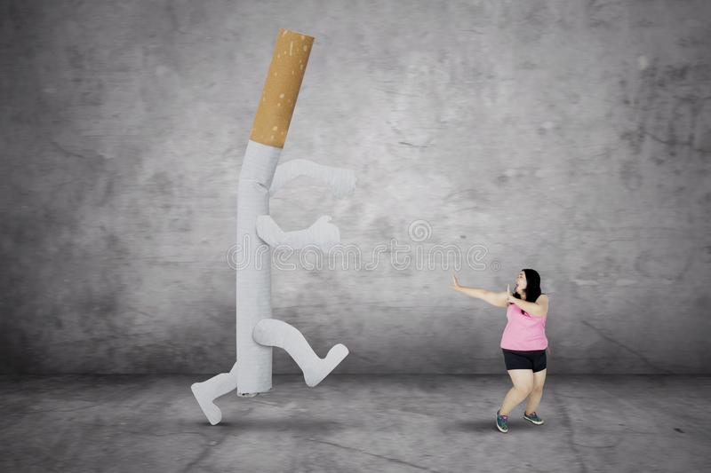 Fat woman escaping from a cigarette. Concept of quit smoking. Fat woman looks afraid while escaping from a cigarette royalty free stock photo