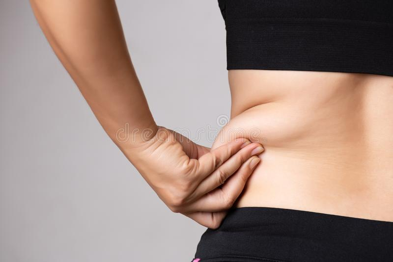Fat woman hand holding excessive belly fat. Healthcare and woman diet lifestyle concept to reduce belly and shape up healthy. Stomach muscle royalty free stock image