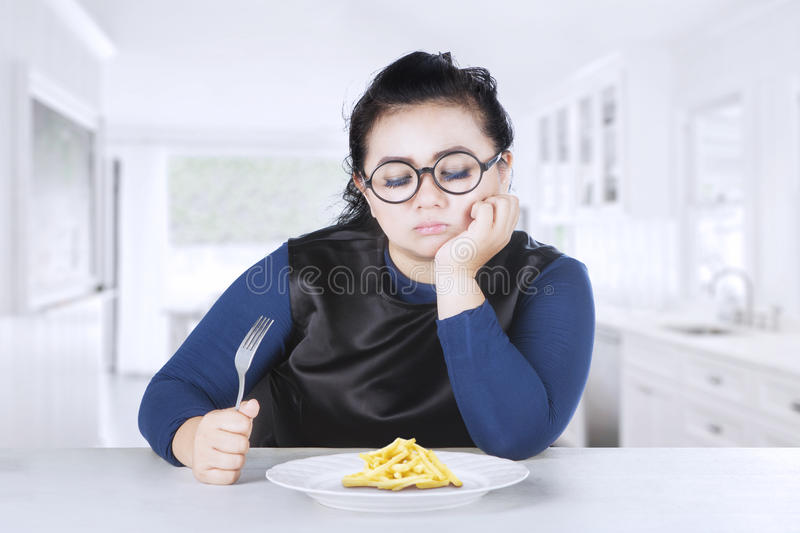 Fat woman holds fork with french fries stock photography