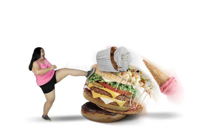 Fat woman kicking tasty foods on studio. Image of fat woman kicking tasty foods to lose weight, isolated on white background royalty free stock image