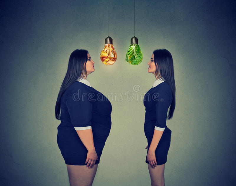 Fat woman looking at happy slim fit girl. Diet choice concept stock images