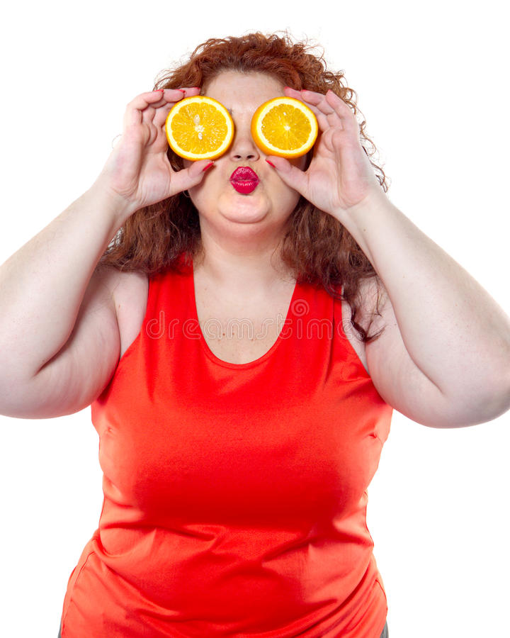 The fat woman with orange juice vegetable fruit holding isolated. On the white background royalty free stock image