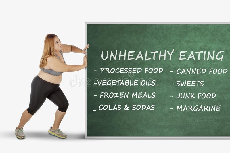 Fat woman pushing chalkboard with her problems stock photography