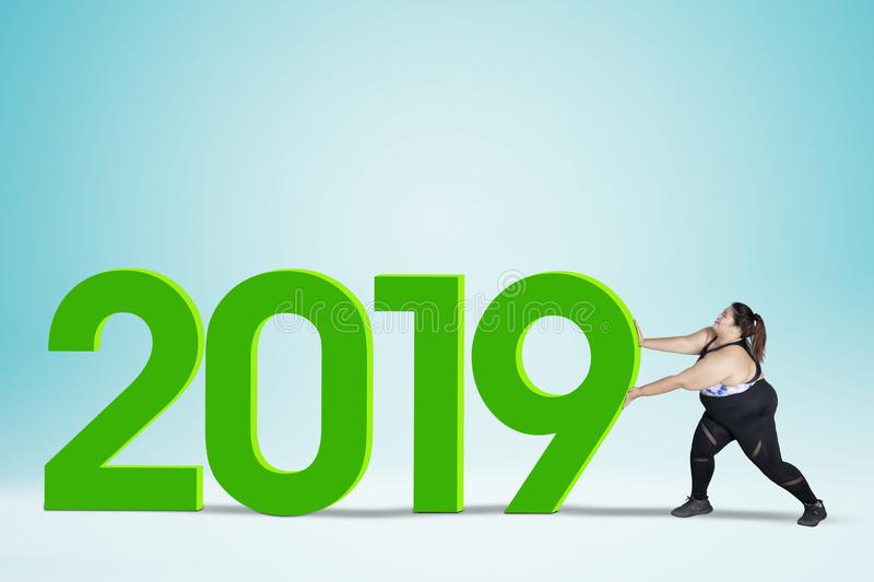 Fat woman pushing numbers 2019 stock photo
