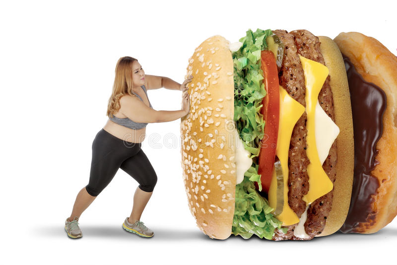 Fat woman pushing tasty foods on studio royalty free stock images