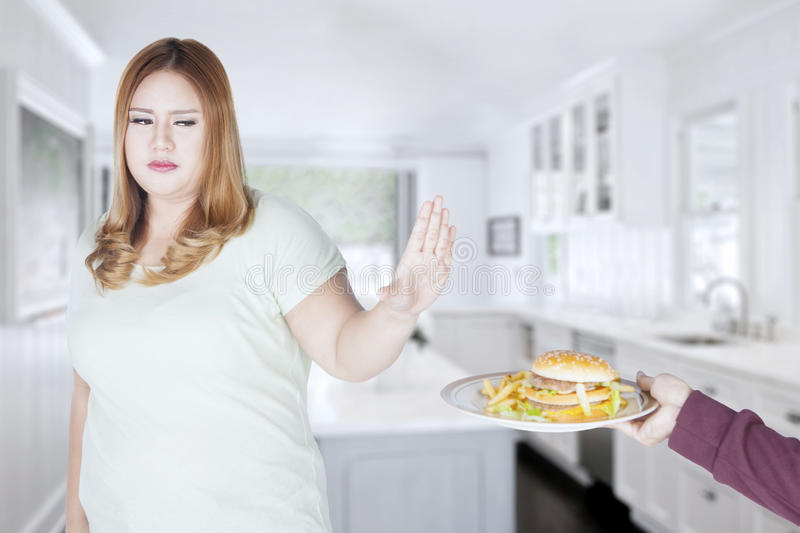 Fat woman refusing to eat hamburger. Photo of overweight blonde woman is refusing to eat hamburger on the plate while standing in the kitchen stock images
