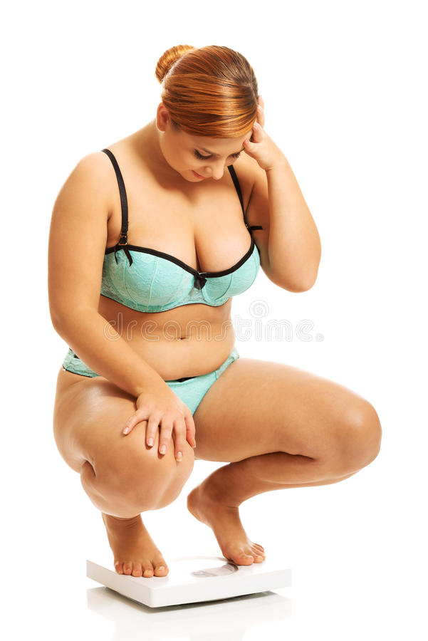 Fat woman squats on scale royalty free stock photography