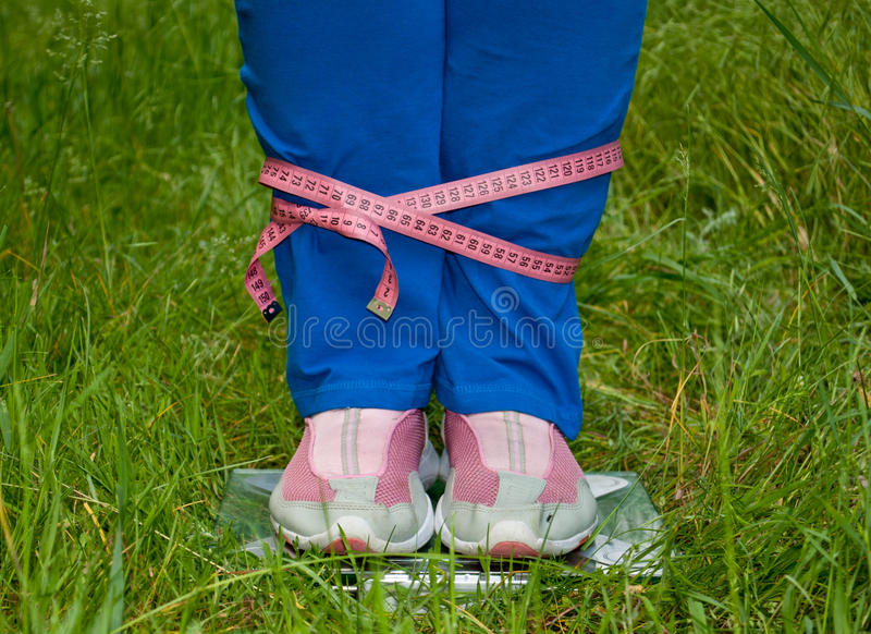 Fat woman is standing on the scales legs connected pink measuring tape stock photos