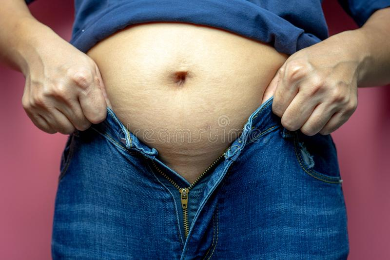 Fat woman trying to wear jeans, Overweight fat woman, Weight losing, obesity, cellulite, health care concept.  royalty free stock photography