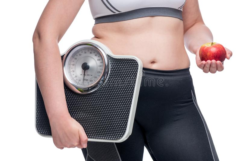 fat woman with weights and an apple makes a choice in favor of sports and healthy eating stock images