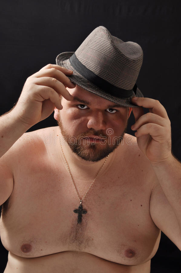 Fat young man. This picture represents a fat young an wearing hat stock photo