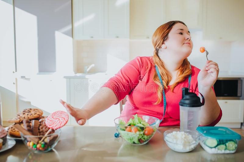 Fat young woman in kitchen sitting and eating healthy food. She show stop sign to sweet food and don`t look at it. Plus. Size model hold for with tomato on it stock image