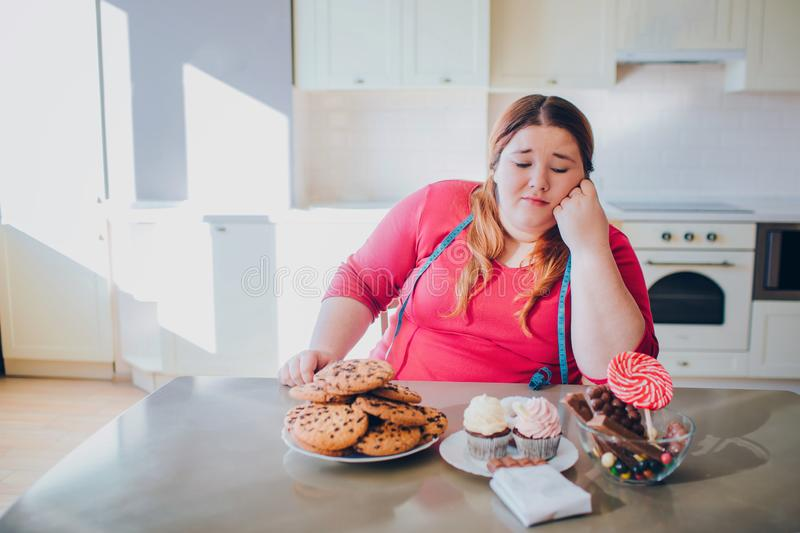 Fat young woman in kitchen sitting and eating sweet food. Bored plus size model look at pancakes and sweets on table stock photos