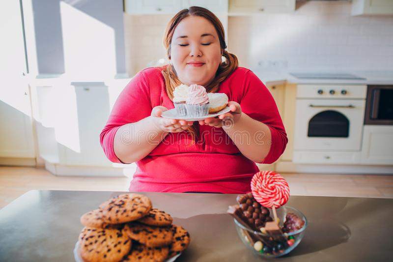 Fat young woman in kitchen sitting and eating sweet food. Plus size model hold small cakes in hands and look at them. Happy woman likes to eat. Body positive royalty free stock images