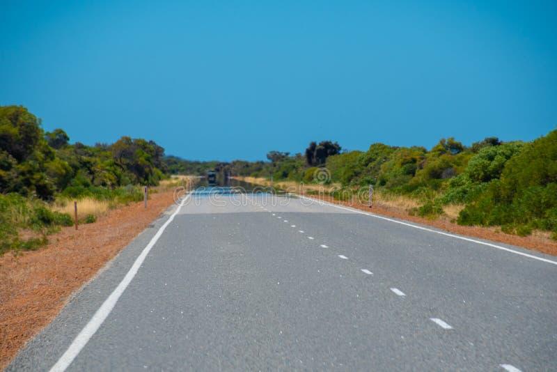 Fata Morgana hägringvisning på den varma vägen i Australien arkivbilder